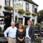Steve and Josie Slayford, former owners of The Running Horses pub in Surrey, now become its lessees after a successful sale to Brakspear in a deal finalised by chief executive Tom Davies (r)