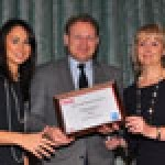 Mark Lewsey, director of communications for the Corinthia Hotel, London (centre), collects one of the hotel's two Hotel Marketing Association (HMA) awards from Hana Lear, client services director at American Express (left) and Linda Moore, HMA chairman (right)